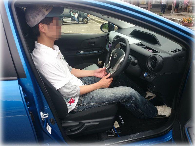 アクアの運転席に座る男性